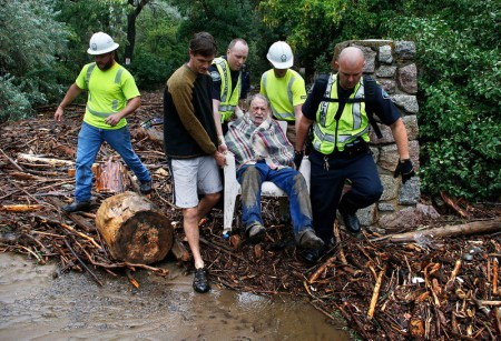 Will Pitner is rescued by emergency workers, and neighbor Jeff Writer, left, after a night trapped sheltering outside on high ground above his home as it filled with water from a surge of water, after days of record rain and flooding, at the base of Boulder Canyon, Colo., Friday Sept. 13, 2013 in Boulder.  (AP Photo/Brennan Linsley)